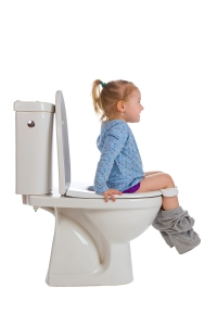Little girl sitting on a toilet